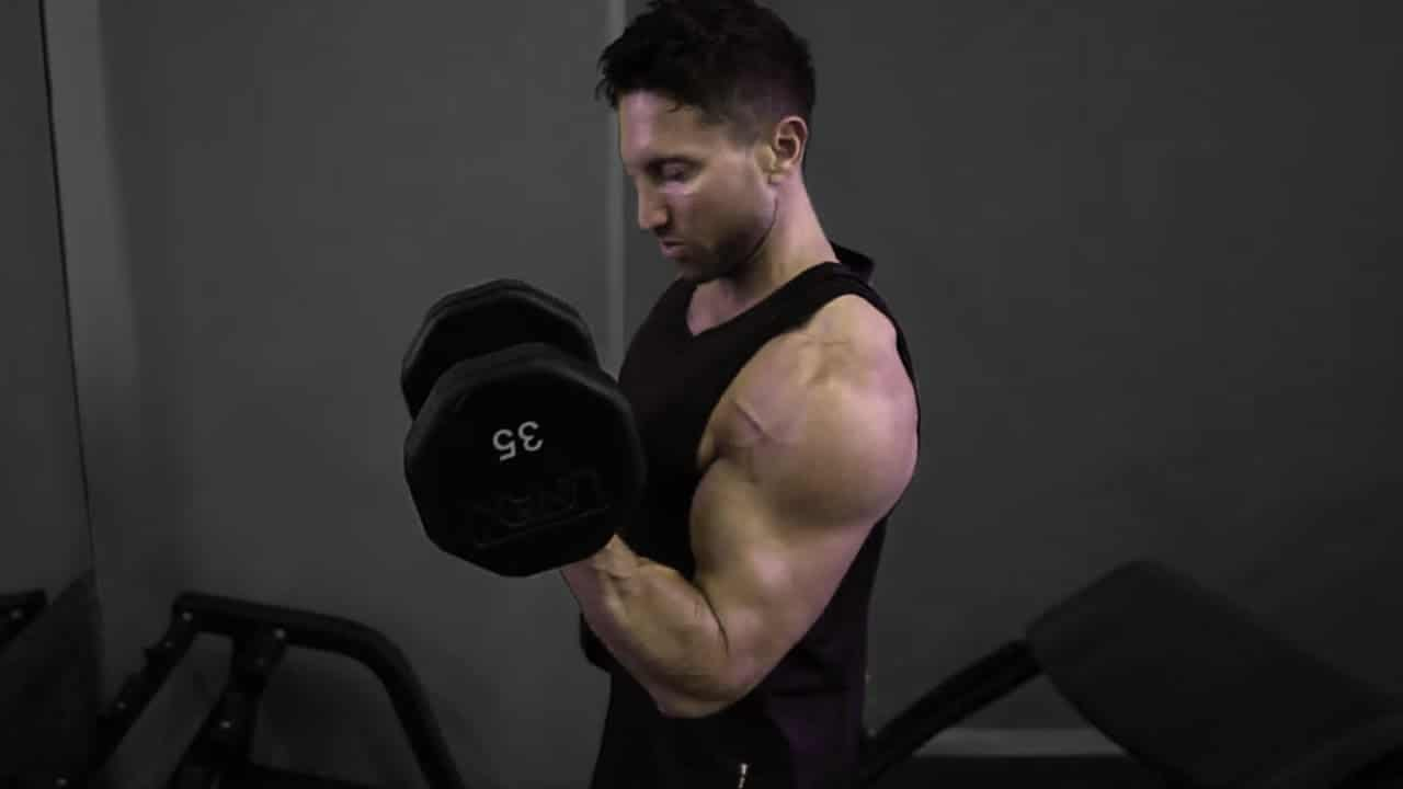 Troy performing supinated bicep curls as part of a superset for arms