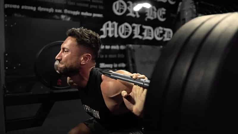 Troy performing a squat at the gym with a black barbell on his back