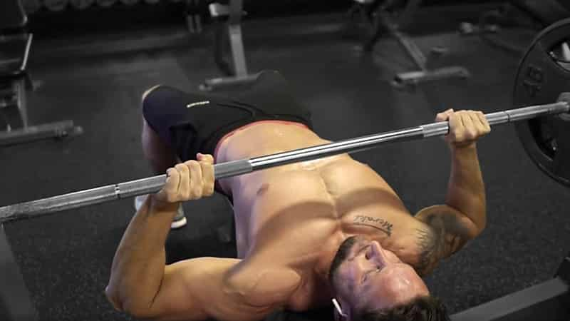 Troy performing a barbell bench press exercise at the gym