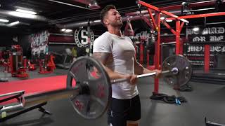 Troy performing cheat curls at the gym