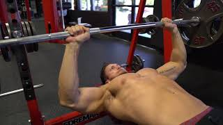 Troy Adashun pushing the barbell when performing a bench press at the gym