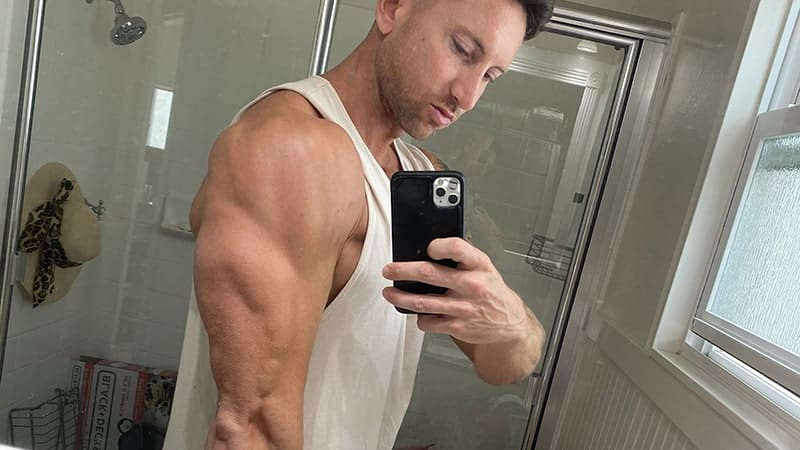 Troy taking a selfie showing his biceps