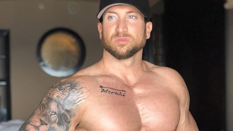 Troy Adashun wearing a black baseball cap and no shirt