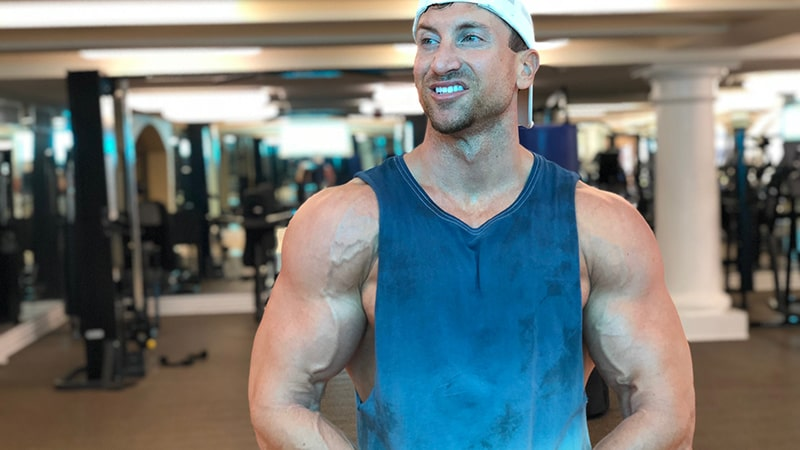 Troy wearing a white baseball cap and blue tank top smiling at the gym