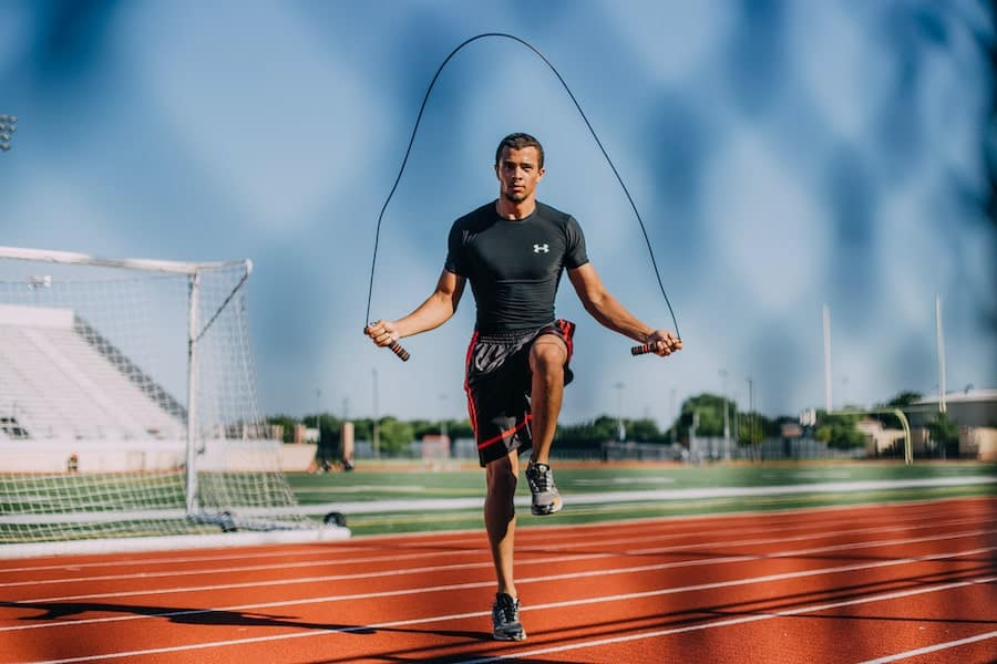 a young man jumps rope on the track of a football field