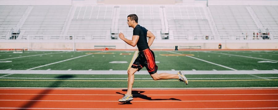 a young man runs on the track around a football field