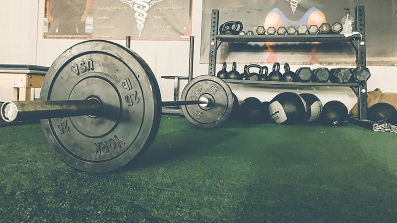 a barbell on a green gym floor and other gym equipment on racks