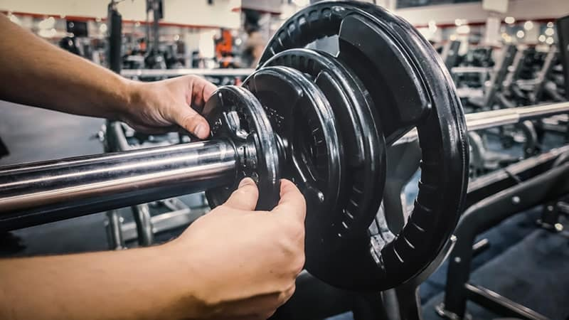 man loading weights on bench press exercise station at the gym
