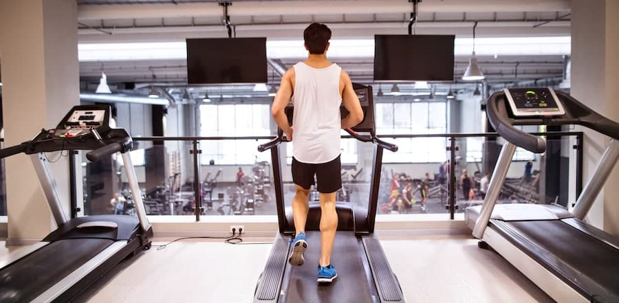 young fit hispanic man in gym running on treadmill