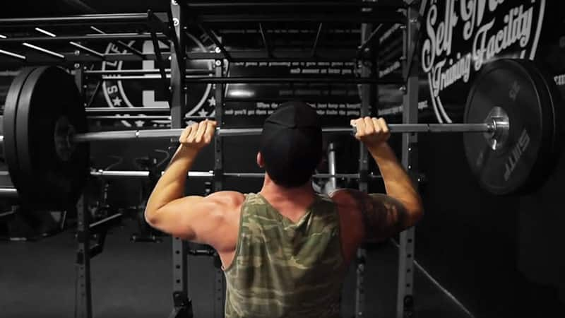 Troy doing a barbell overhead press at the gym wearing a camouflage top
