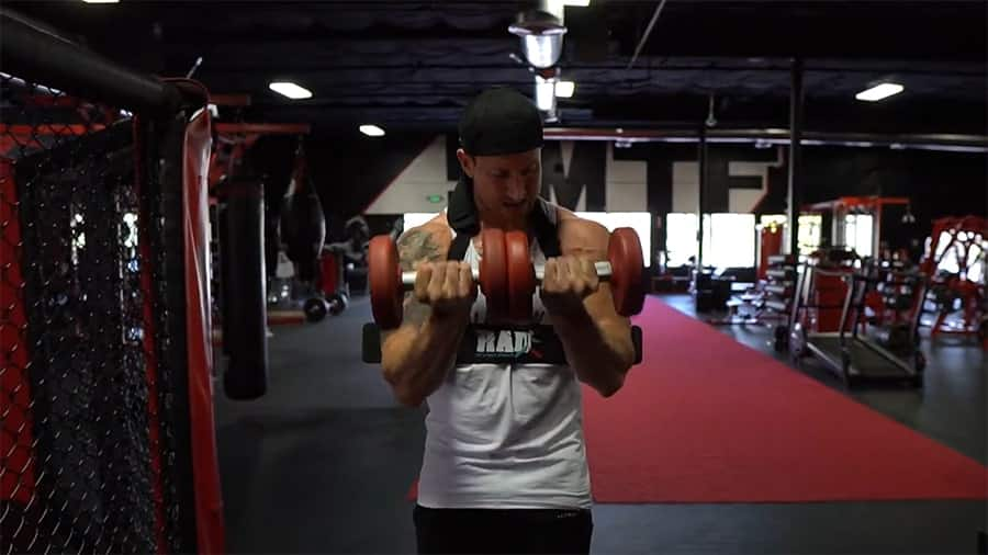 Troy doing a supinated dumbbell curl using a bicep blaster