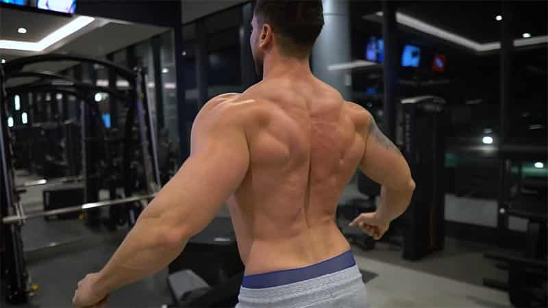 Troy flexing his back muscles at the gym