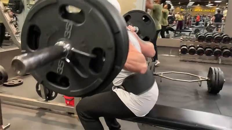 Troy holding a barbell while doing box squats