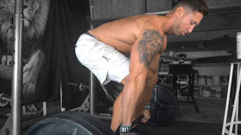 Troy lifting a barbell for a deadlift exercise in his garage