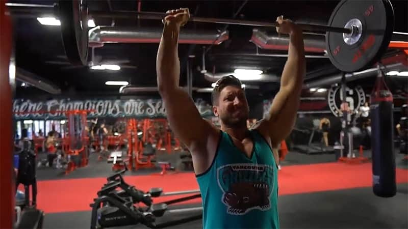 Troy performing a barbell overhead press at the gym wearing a blue top