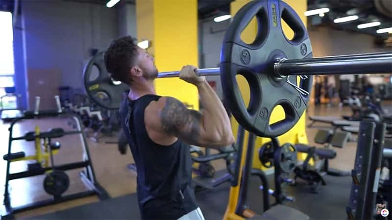 Troy performing a barbell overhead press with correct grip