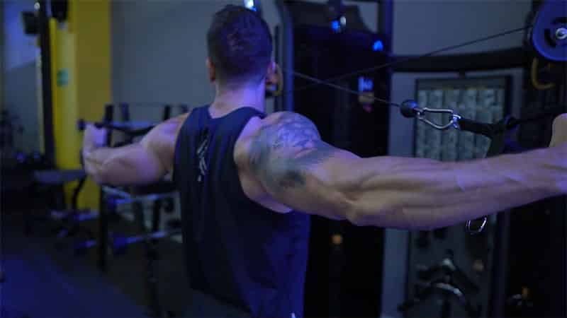 Troy performing a cable rear delt fly at the gym