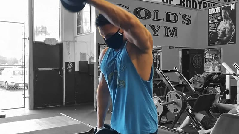 Troy performing a dumbbell alternate front raise at the gym