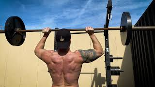 Troy performing a standing barbell overhead press outside