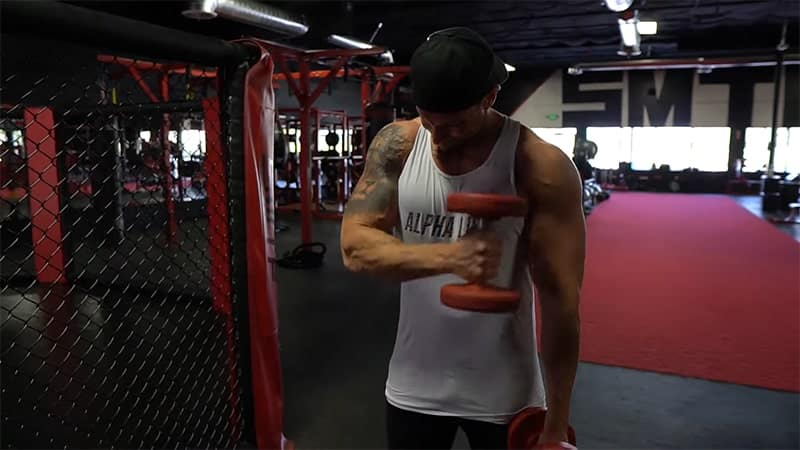 Troy performing the bicep 21s exercise with dumbbells without momentum