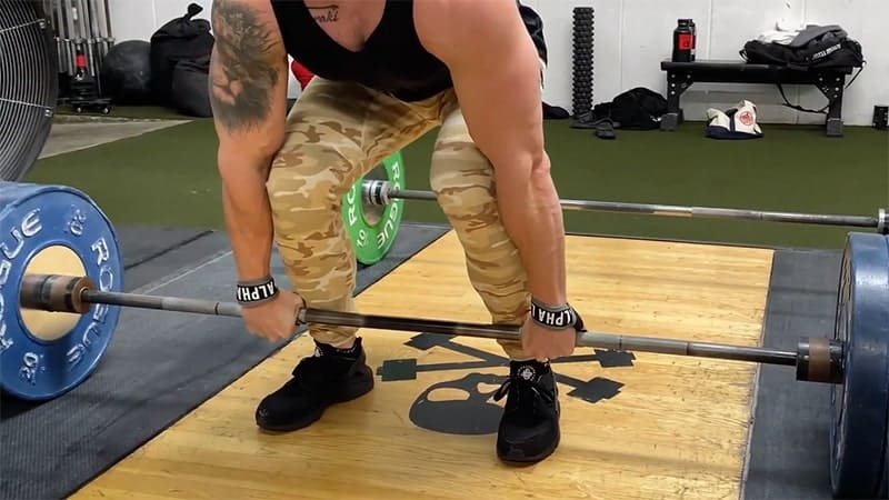 Troy preparing to lift a barbell for a barbell deadlift exercise