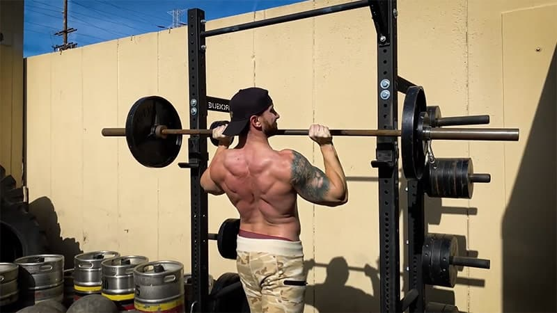 Troy unracking the bar for a barbell overhead press outside