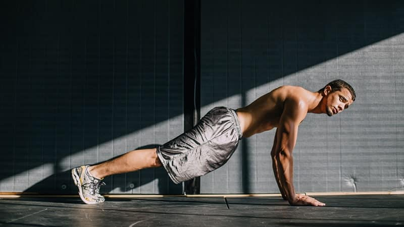 a young man performs a plank exercise in a lower ab workout