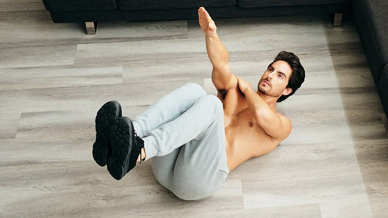 adult man training abs muscles at home