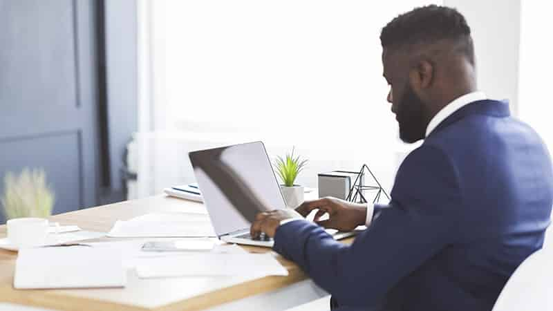 back view of young businessman working with laptop