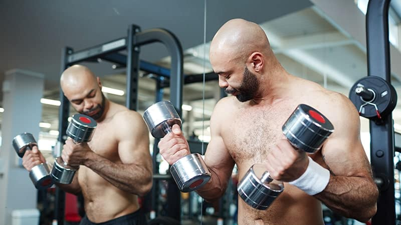 fit bald man working out with dumbbells by mirror