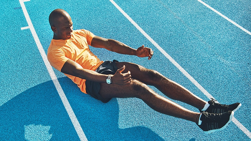 fit young athlete doing crunches on a running track