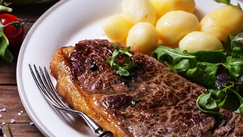 grilled steak with potatoes and salad