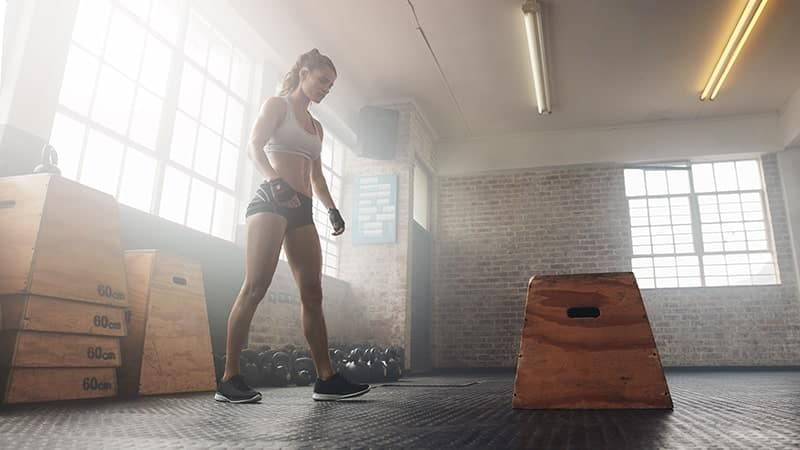 muscular young woman working out with a box at the gym