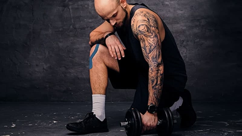 sporty shaved head sporty male standing in knee holding dumbbell