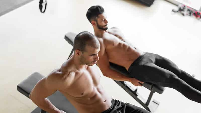 strong men are doing abs crunches on bench