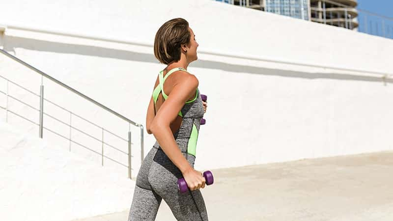 woman with brown short hair running with dumbbells