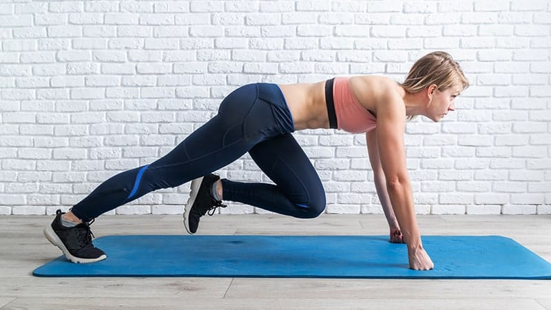 young blond woman doing mountain climber exercise