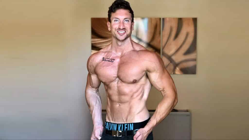 Troy Adashun in his living room without a shirt smiling