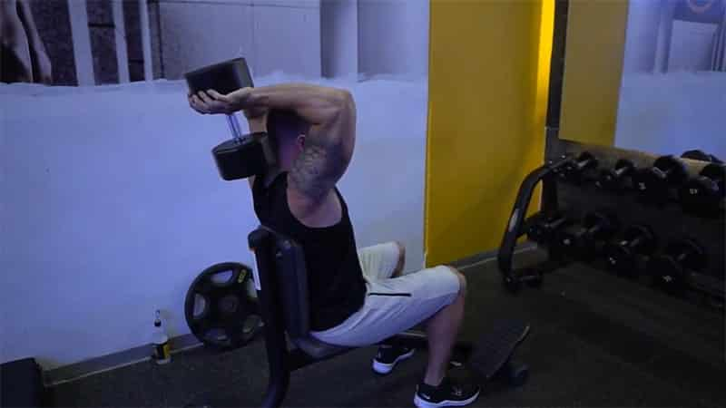 Troy doing an overhead tricep press with correct back posture