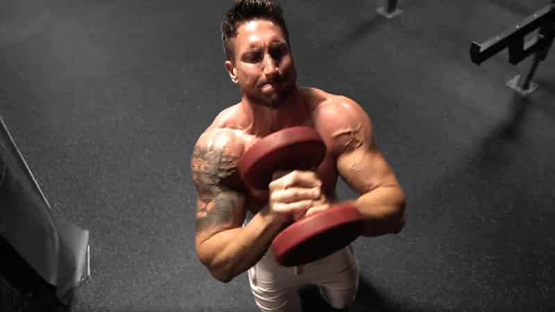 Troy holding a red dumbbell to his chest