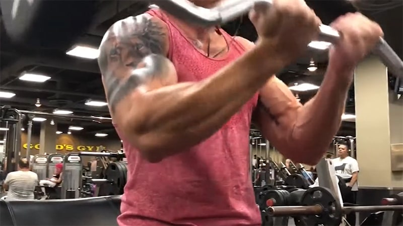 Troy performing a close grip ez bar curl with correct arm form