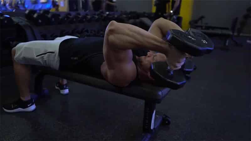 troy performing lying tricep extensions
