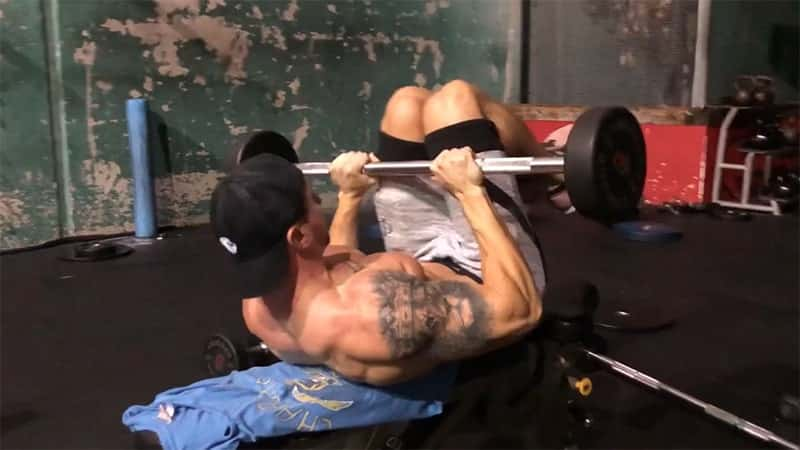 Troy performing weighted ab cocoons on a bench at the gym