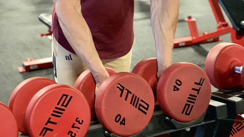 Troy's hands on dumbbells on the rack