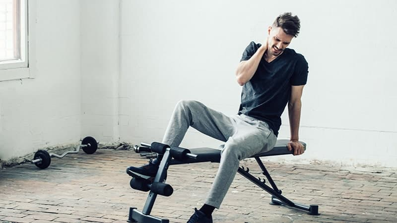 handsome guy in sport gym with neck injury pain