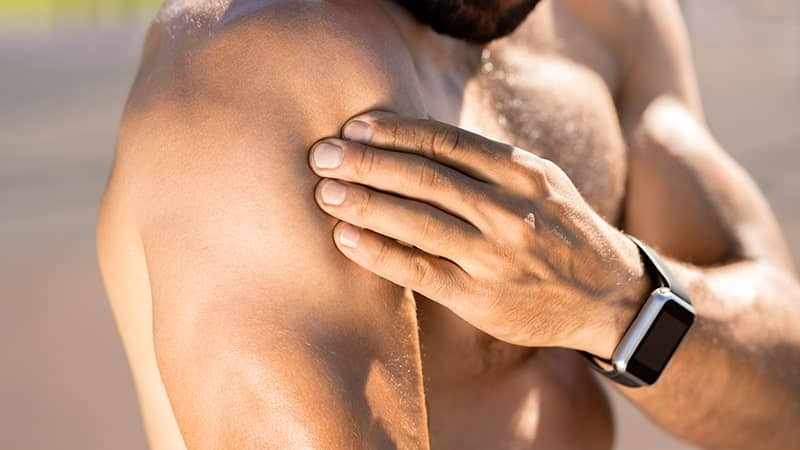 man putting his arm on his shoulder muscles