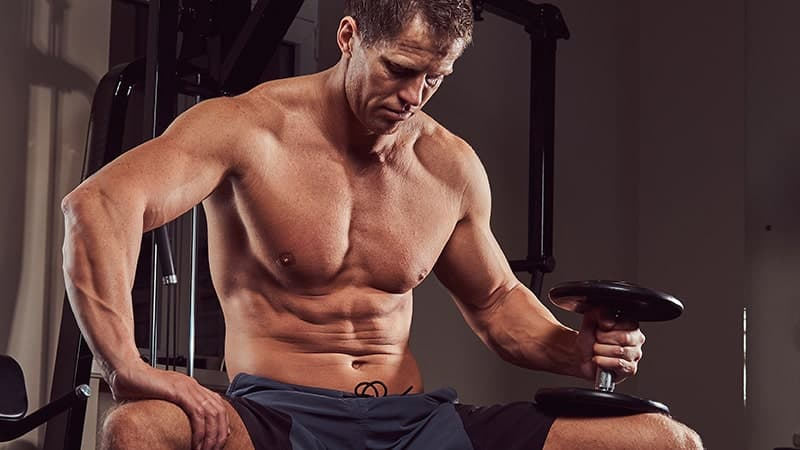 muscular shirtless athlete doing exercise with dumbbells