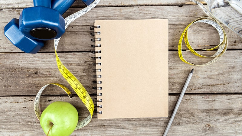 top view of notebook fresh apple measuring tape and dumbbells