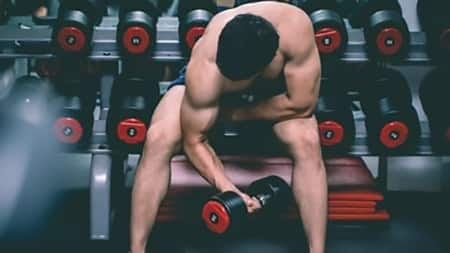 young man performing standing dumbbell concentration curls