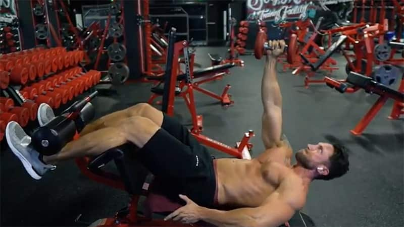 Troy doing a single arm decline crunch at the gym